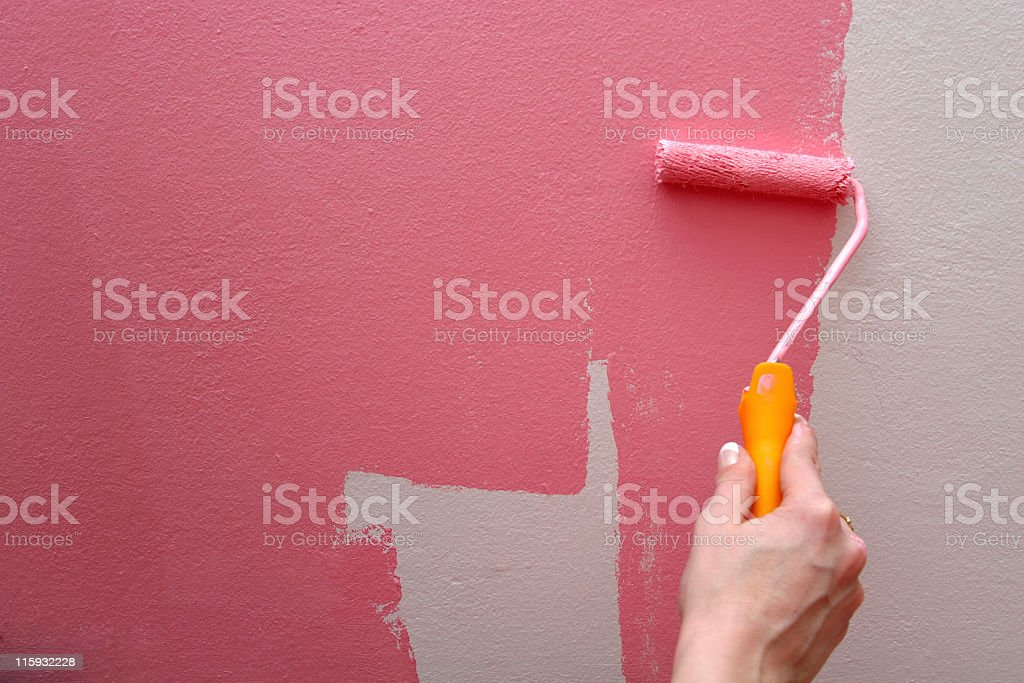 Using a roller to paint pink on a white wall stock photo