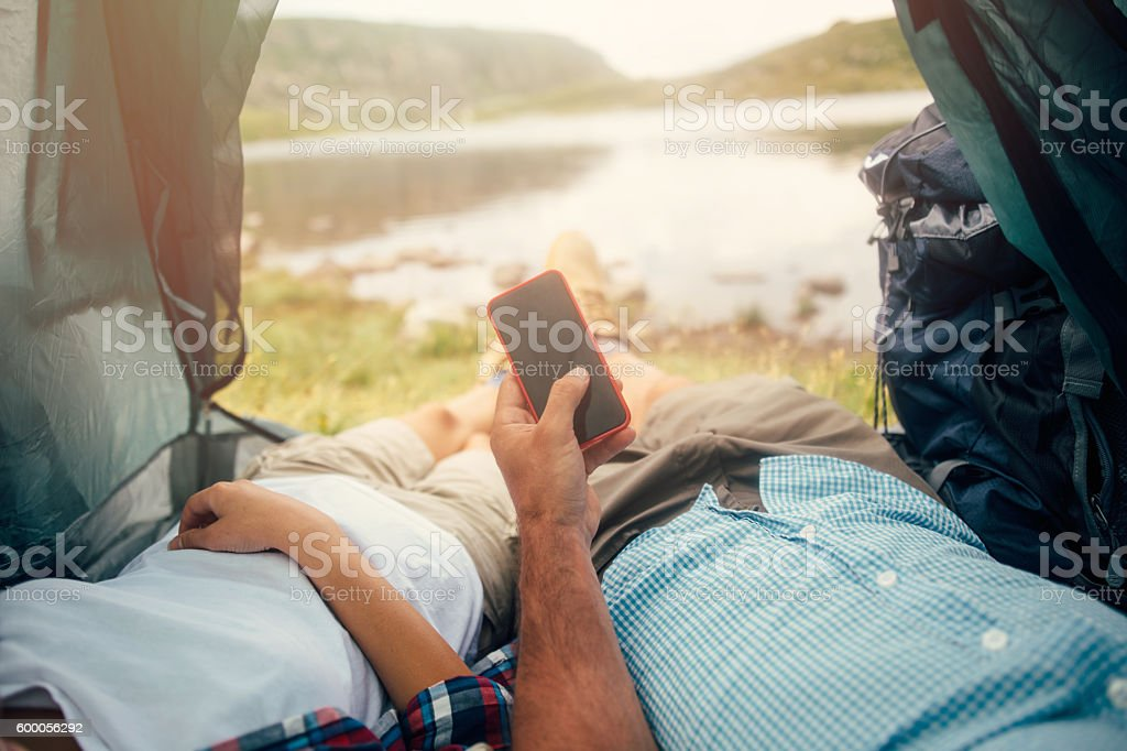 Using a smart phone in a tent stock photo