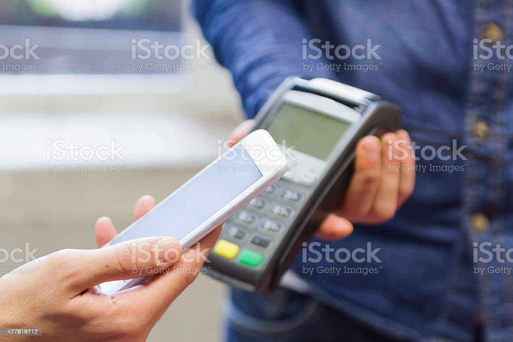 Using a smart phone to pay with a NFC technology stock photo