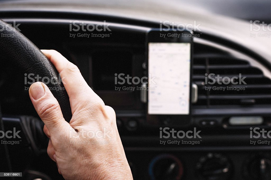 Using a smartphone to navigate the car stock photo