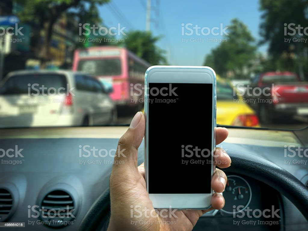 using a smartphone while driving a car stock photo