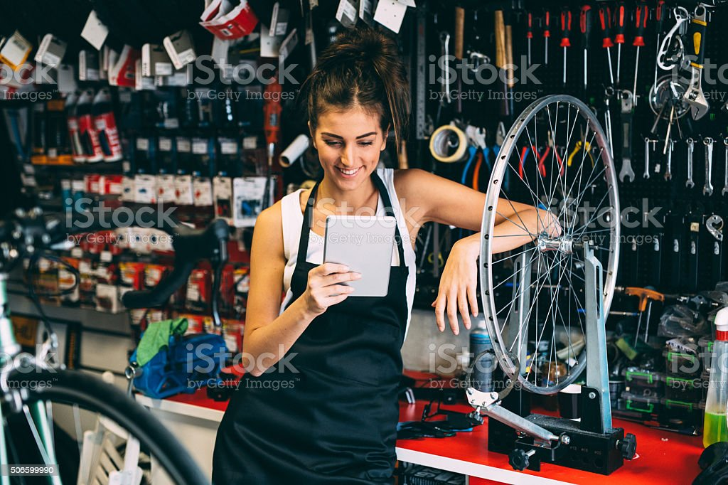 Using a tablet while fixing a bicycle stock photo