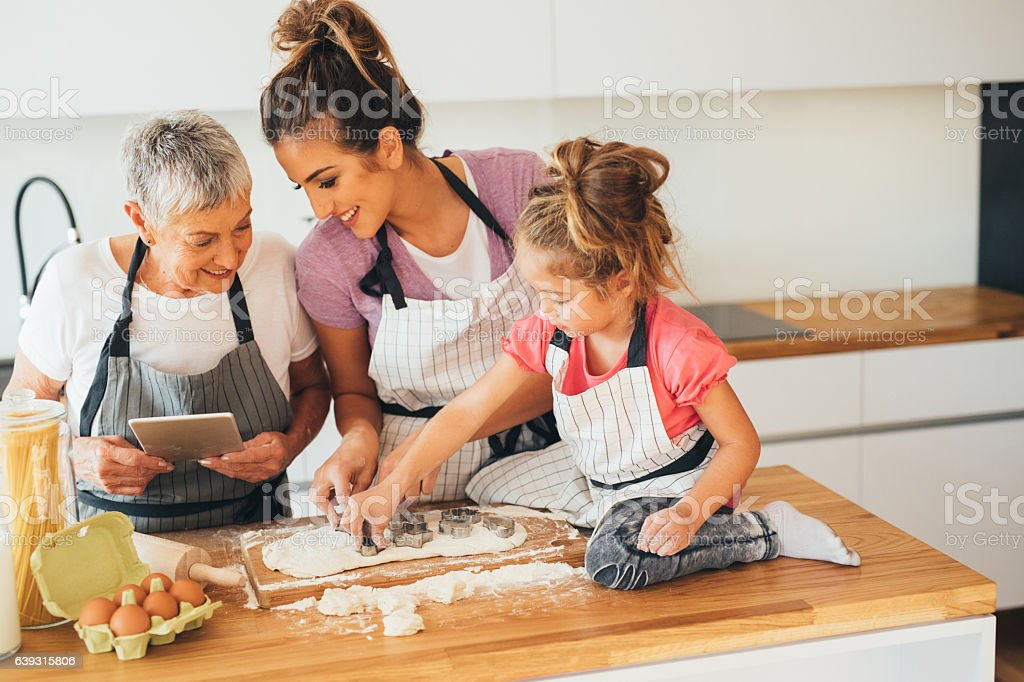 Using a tablet while making cookies stock photo