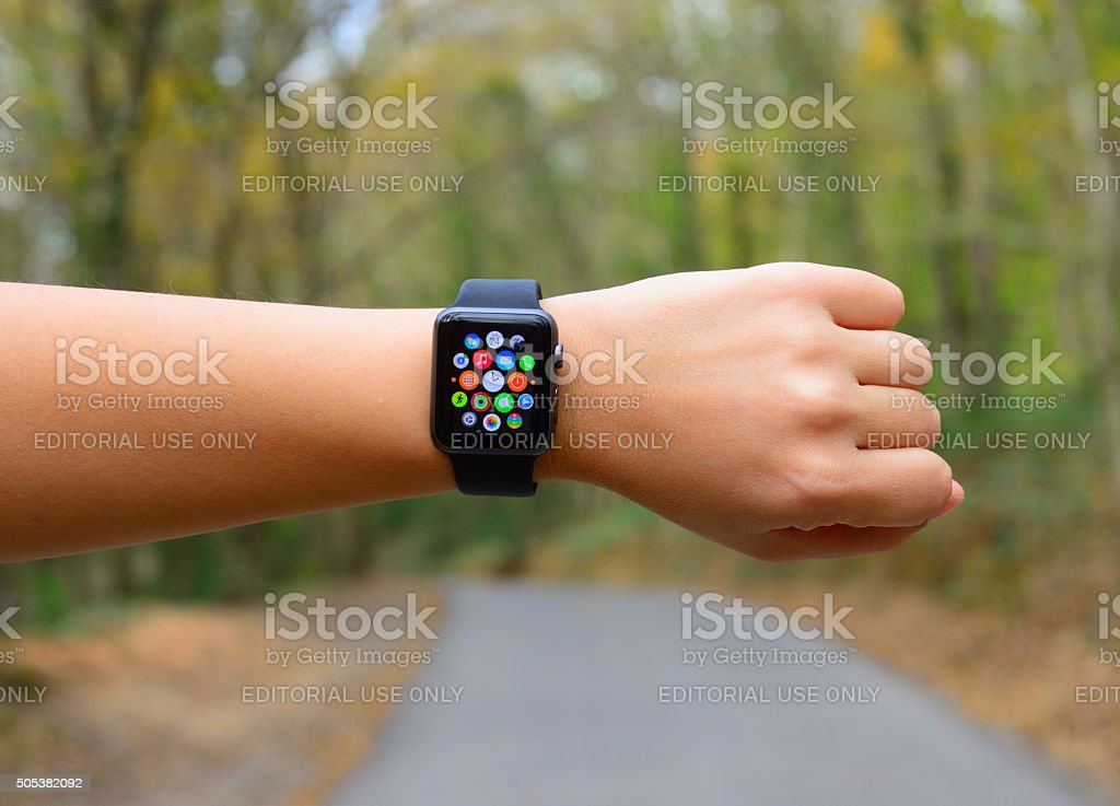 Using Apple Watch Sport in park stock photo