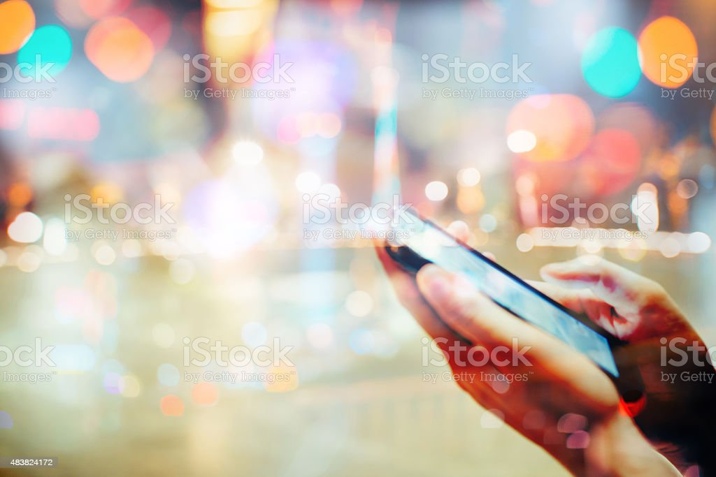 using cell phone in abstract city background double exposure stock photo