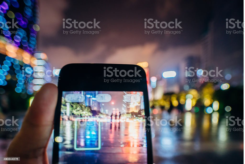 using cell phone take photo at city night, stock photo