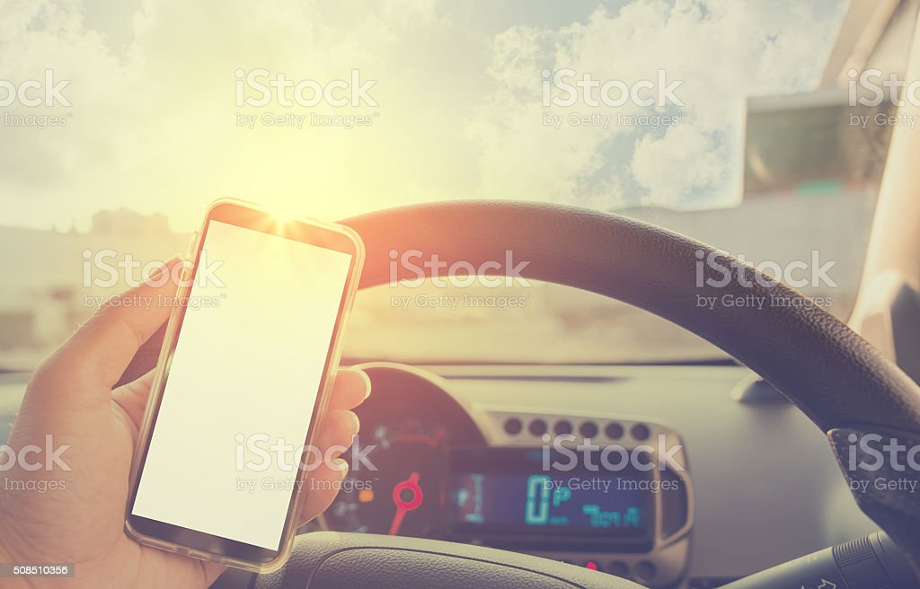 Using cellphone in car - with defocused city traffic. stock photo