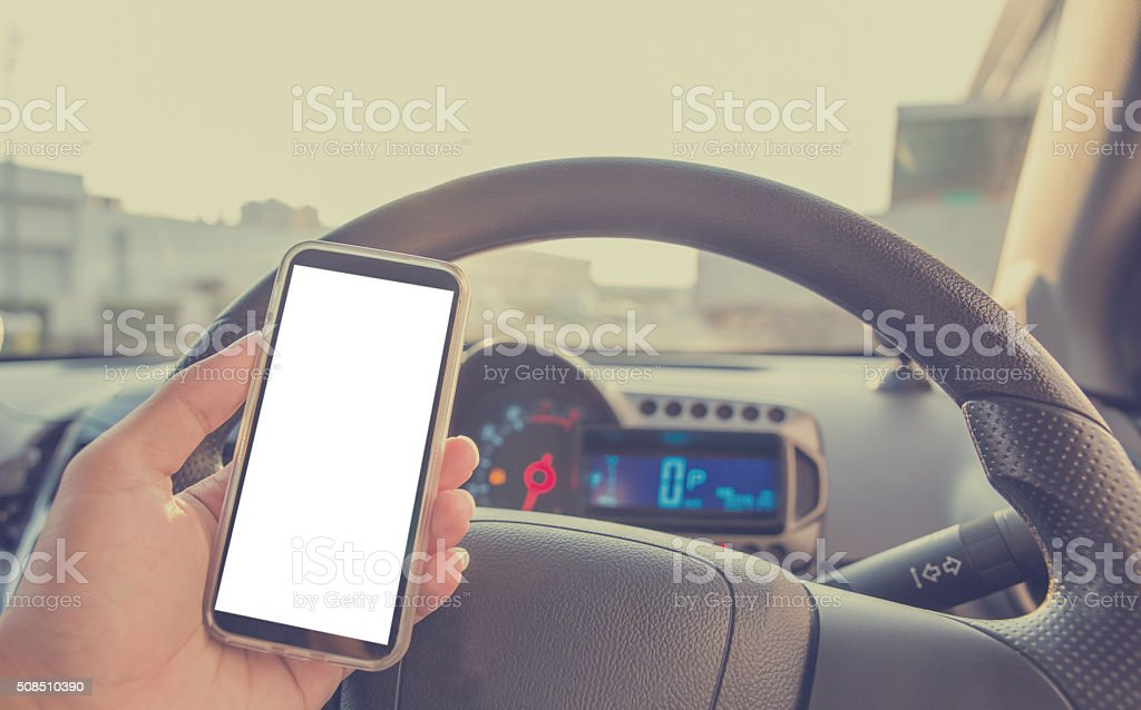 Using cellphone in car with defocused city traffic. stock photo