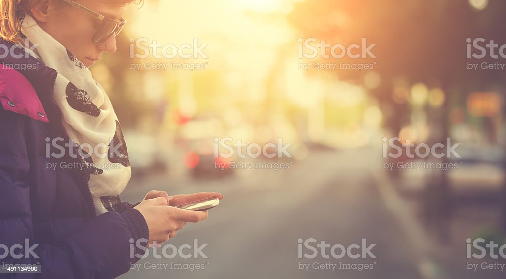 Using cellphone with defocused city traffic stock photo