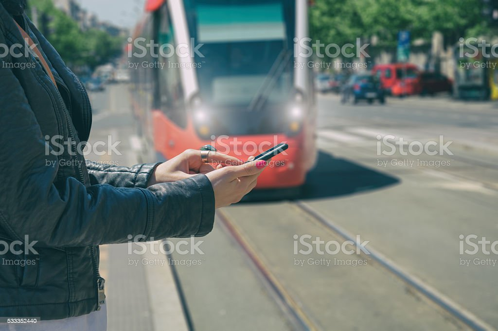Using cellphone with defocused city tram. stock photo
