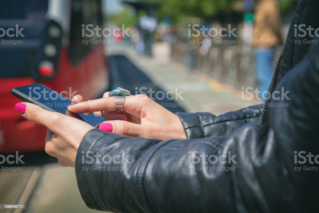 Using cellphone with de-focused city tram. stock photo