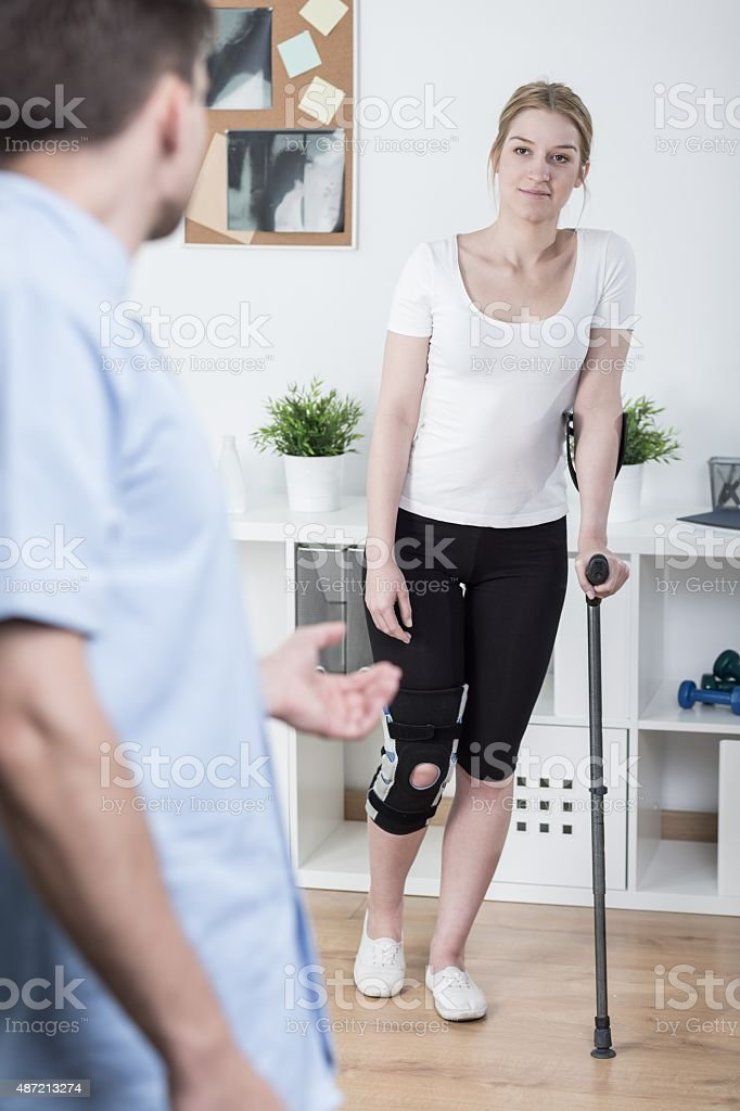 Using crutch after knee injury stock photo
