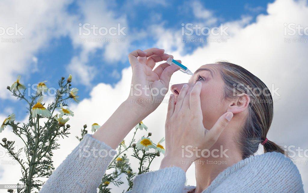 using eyedropper to treat irritated eyes stock photo