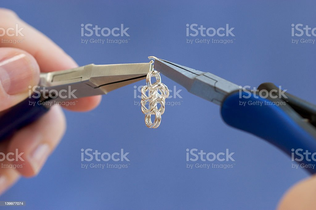 Using flat nose pliers to make silver wire jewelry royalty-free stock photo