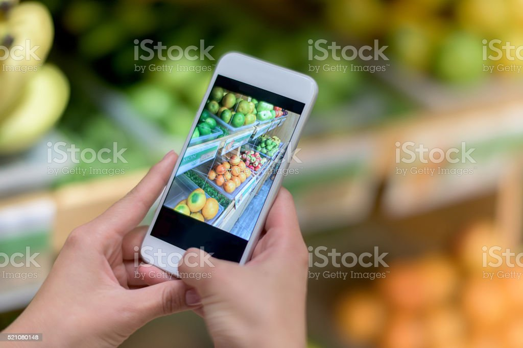 Using food app on a cell phone at the supermarket stock photo