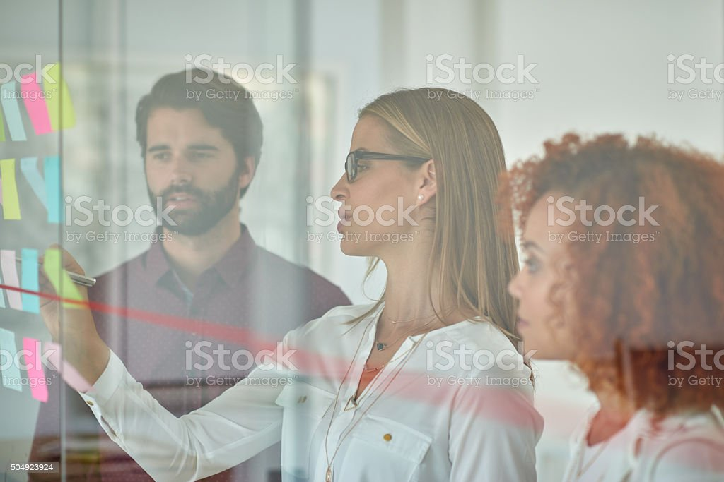 Using glass door to make presentation to her colleagues stock photo