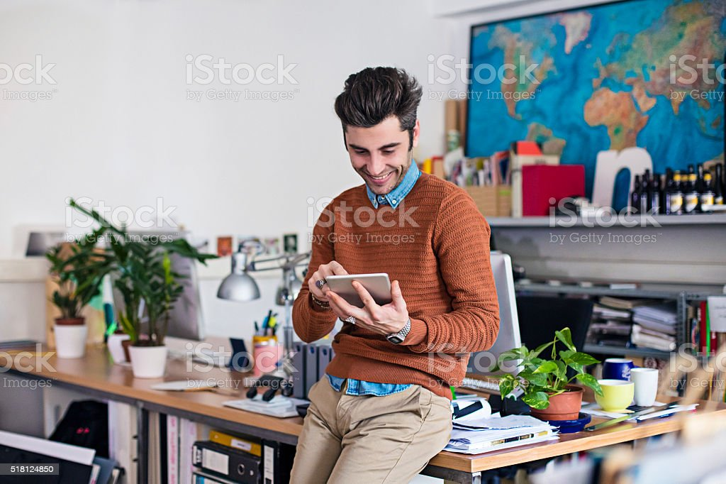 Using his digital tablet in the office stock photo