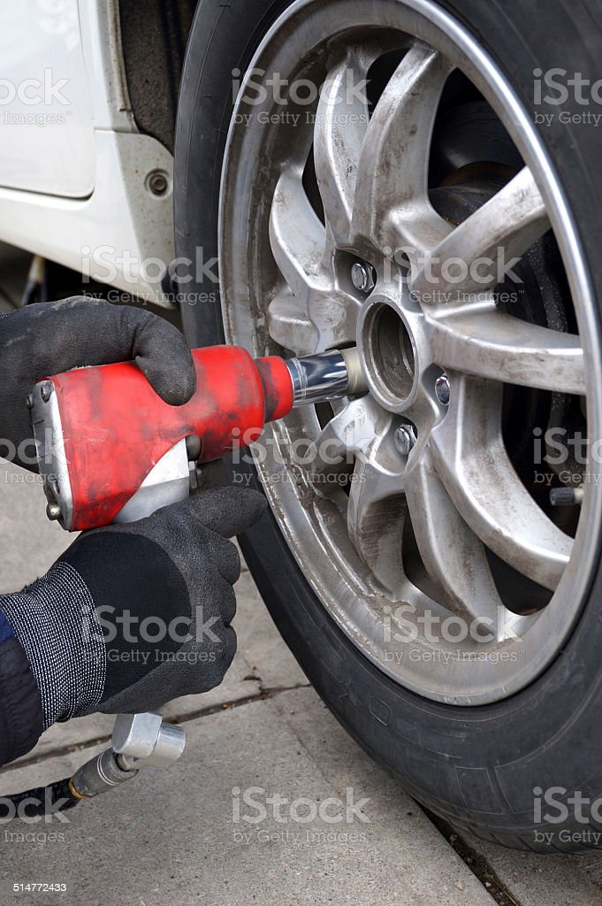 Using Impact Wrench to Change Tires stock photo