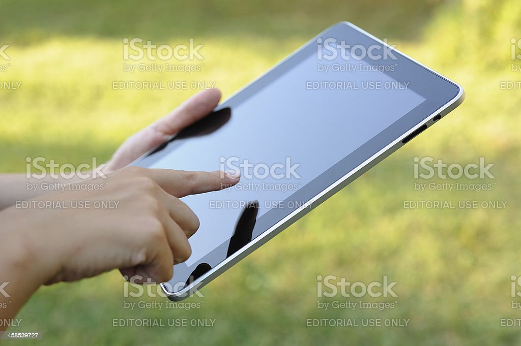 Using iPad in park royalty-free stock photo