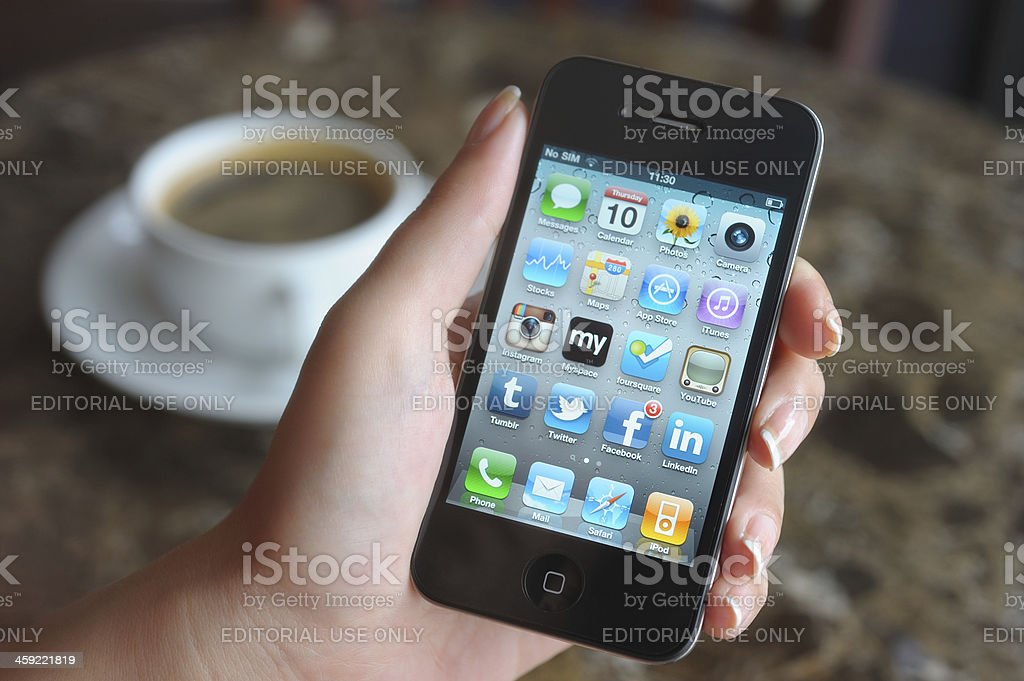 Using iPhone in a coffee shop royalty-free stock photo