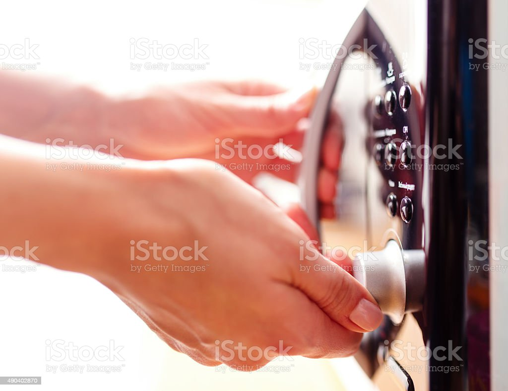Using microwave oven, close up photo, shallow dof stock photo