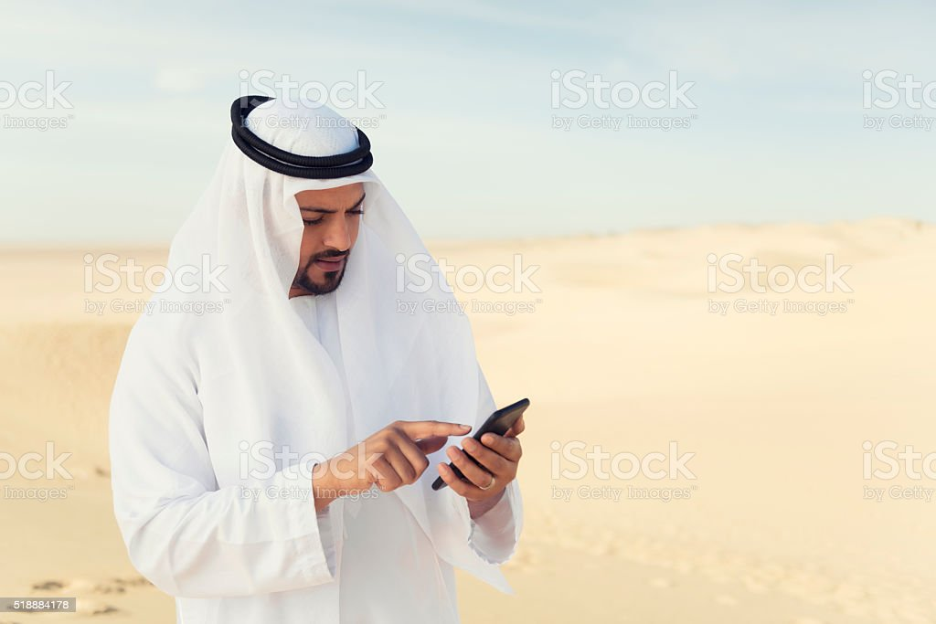 Using mobile phone in the desert stock photo