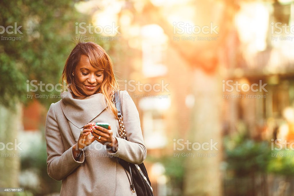 Using Mobile Phone on Her Way From Work stock photo