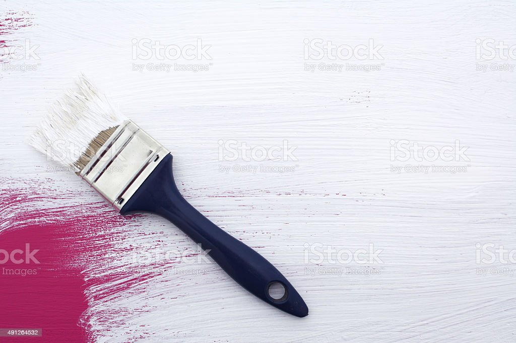 Using paintbrush to paint over pink with white emulsion stock photo
