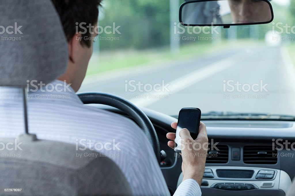 Using phone while driving car stock photo