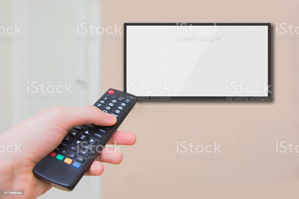 Using remote control to control channels on tv stock photo