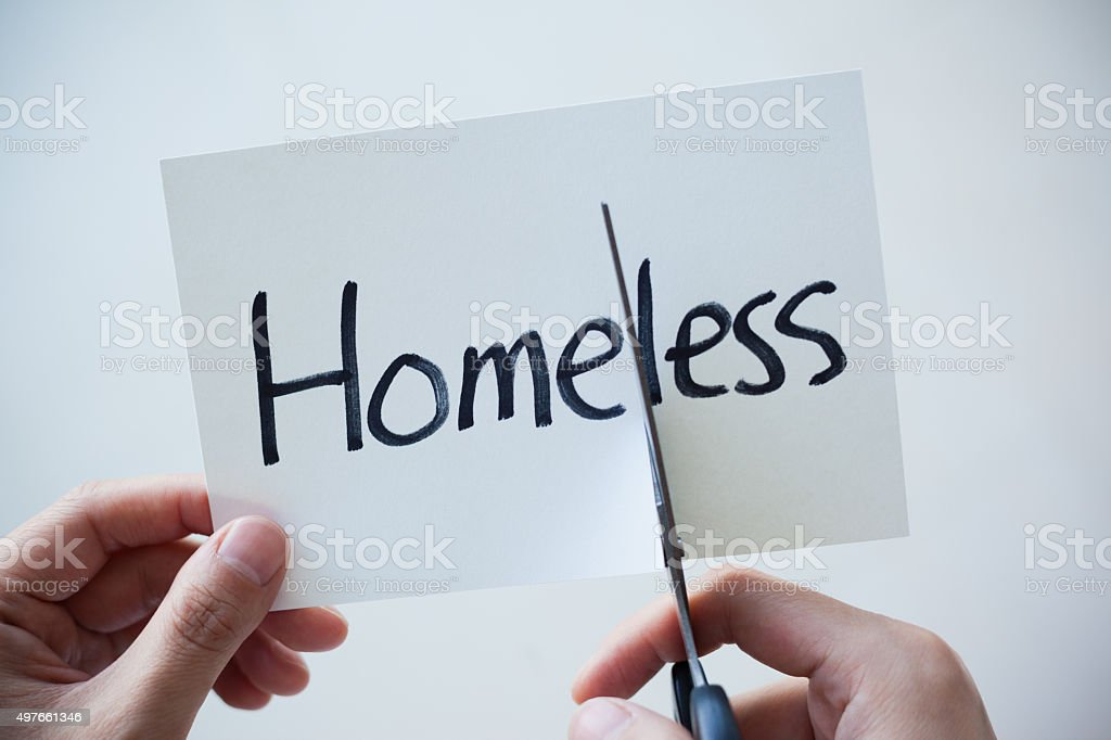 Using Scissors Cut the Word on Paper Homeless Become Home stock photo
