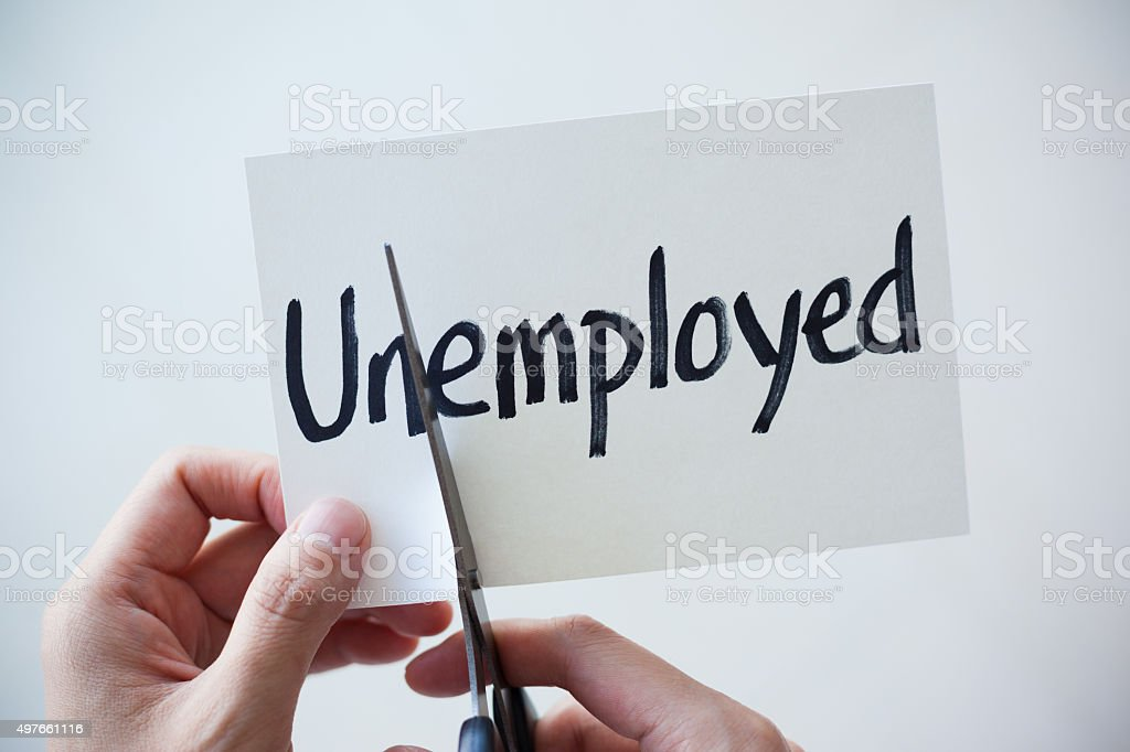 Using Scissors Cut the Word on Paper Unemployed Become Employed stock photo