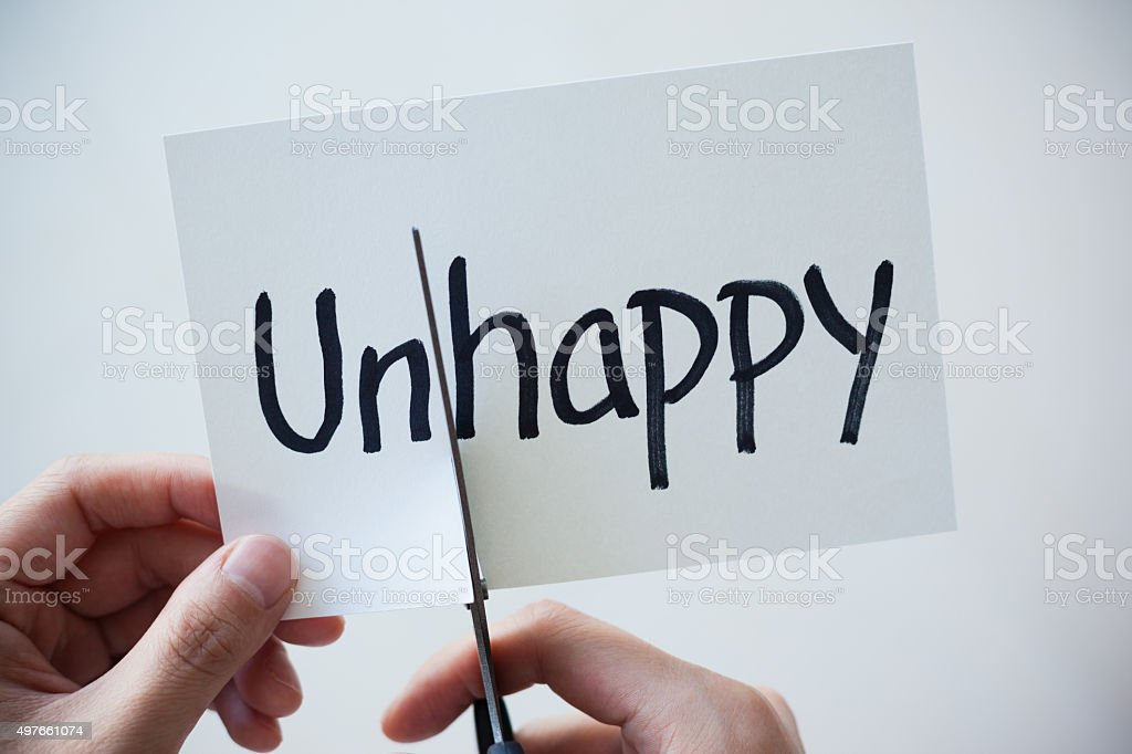Using Scissors Cut the Word on Paper Unhappy Become Happy stock photo