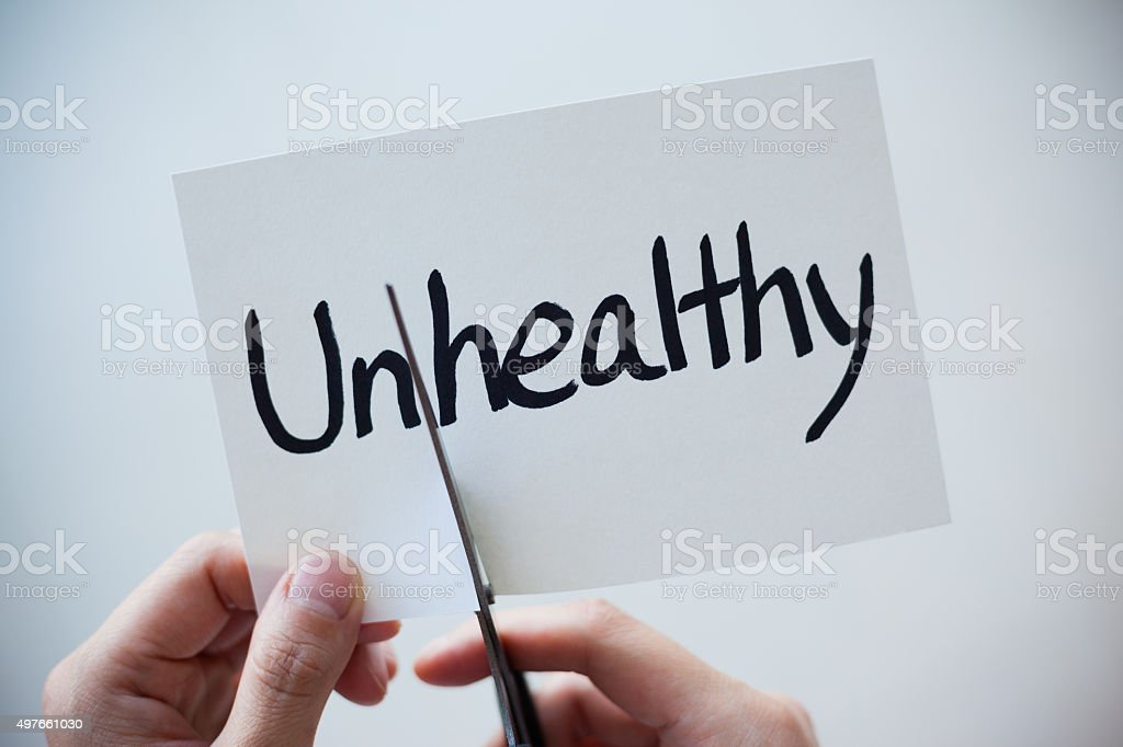Using Scissors Cut the Word on Paper Unhealthy Become Healthy stock photo