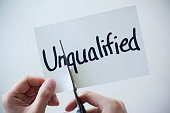Using Scissors Cut the Word on Paper Unqualified Become Qualified