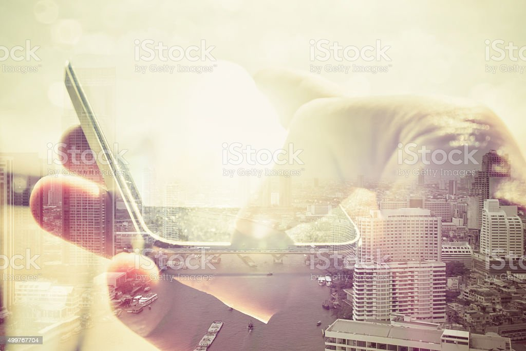 using smart phone and cityscape stock photo