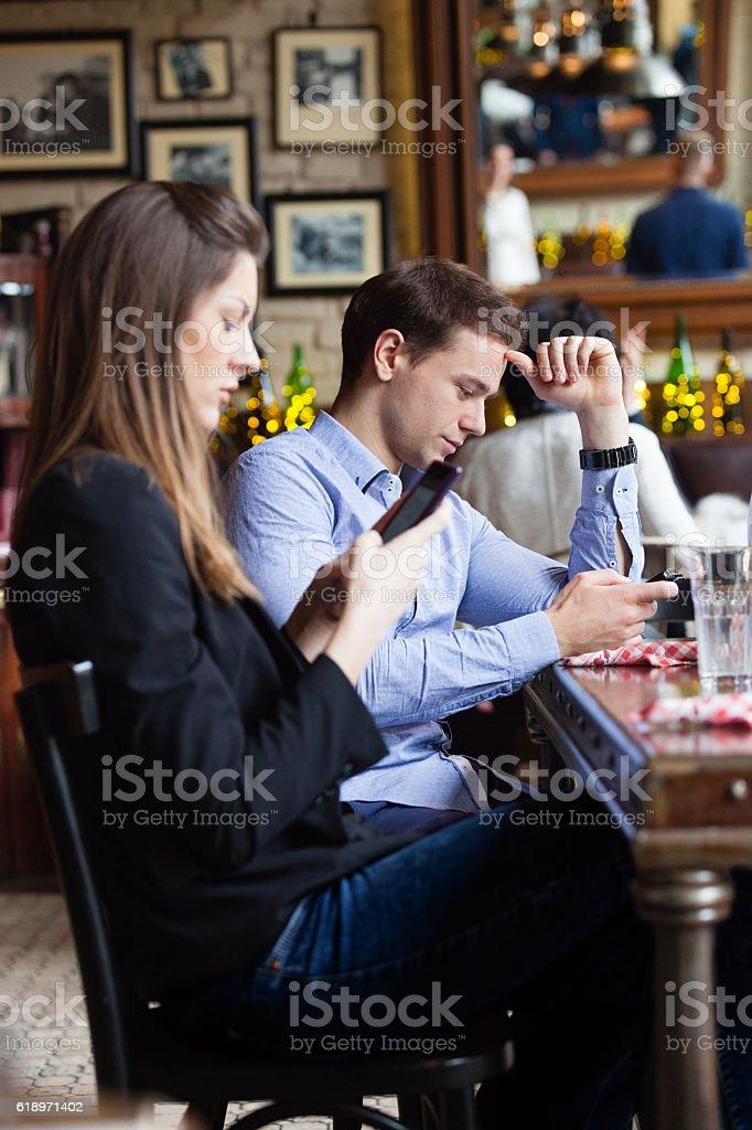Using smart phone in restaurant stock photo