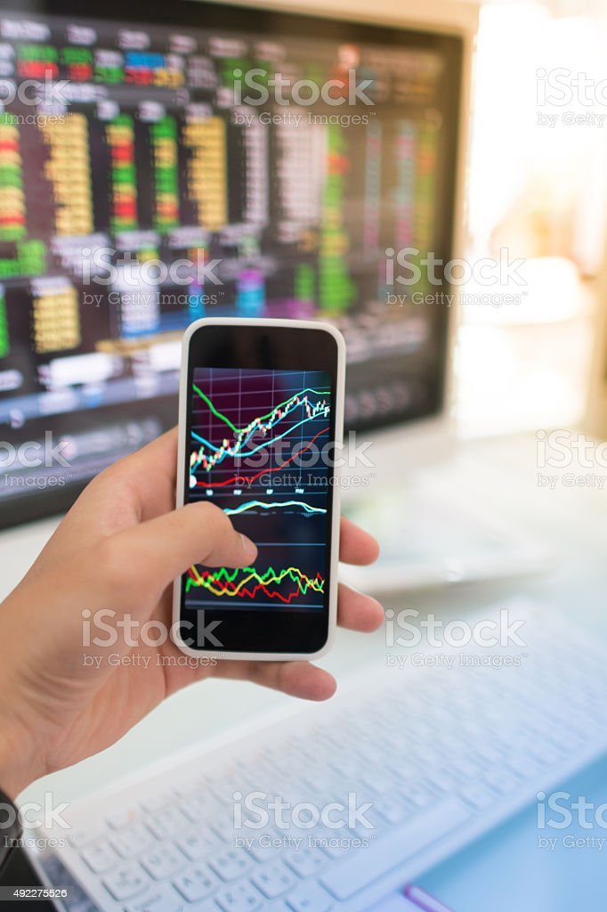 Using smart phone in Stock market graph and office work stock photo