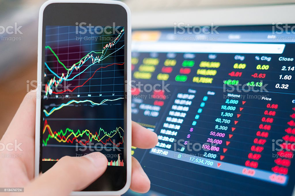 Using smart phone in Stock market graph stock photo