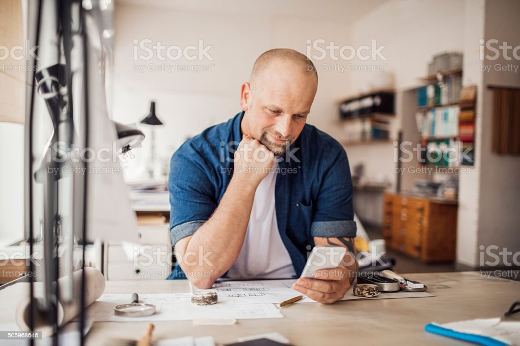 Using smart phone while working stock photo