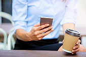 Using smartphone and holding coffee to go close up