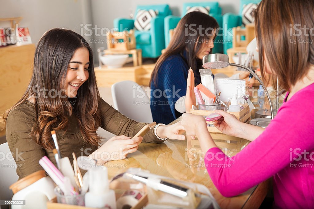 Using smartphone at a nail salon stock photo