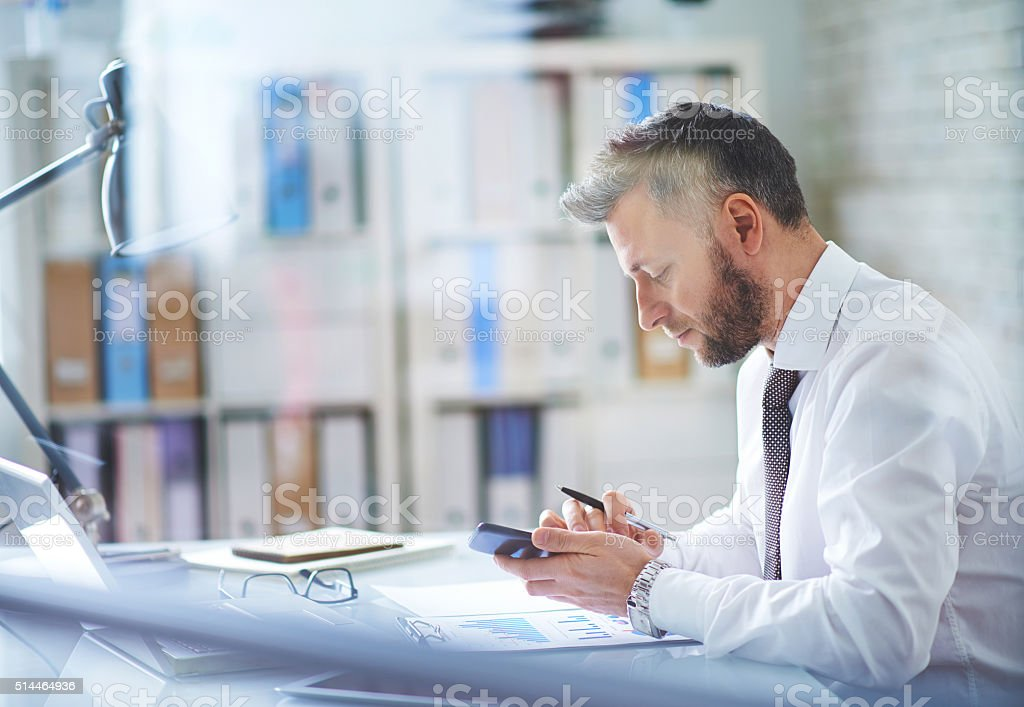 Using smartphone at workplace stock photo