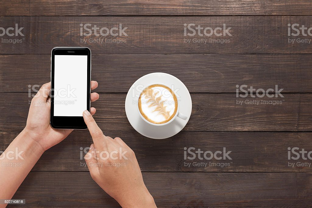 Using smartphone beside of coffee on wooden table stock photo