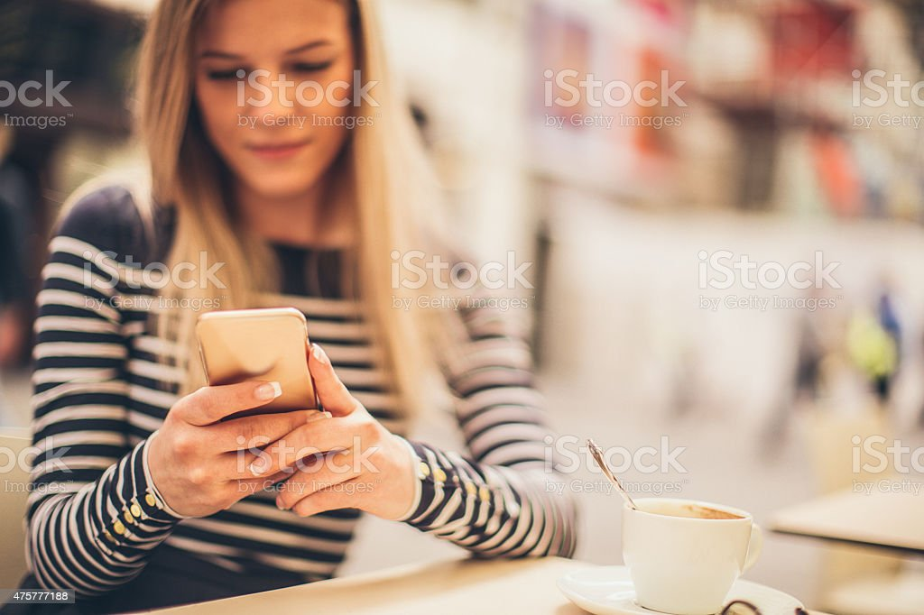 Using smartphone in a cafe stock photo