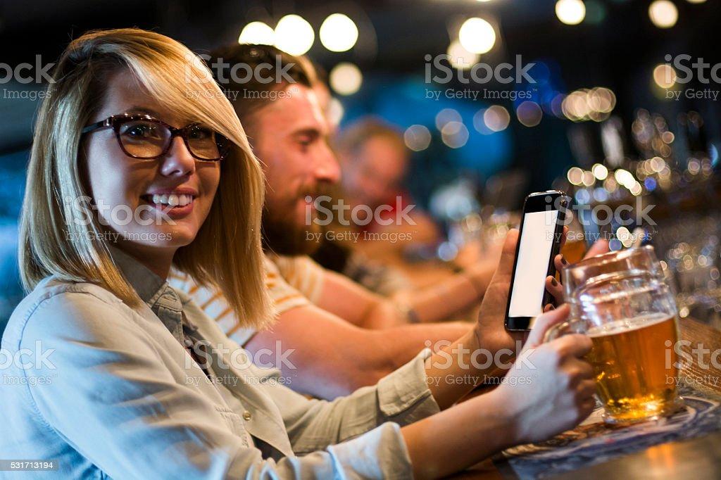 Using smartphone in a pub stock photo
