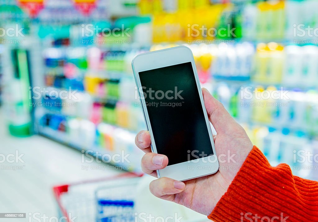using smartphone in supermarket stock photo