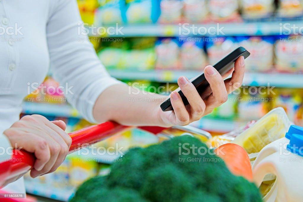 using smartphone in supermarket stock photo