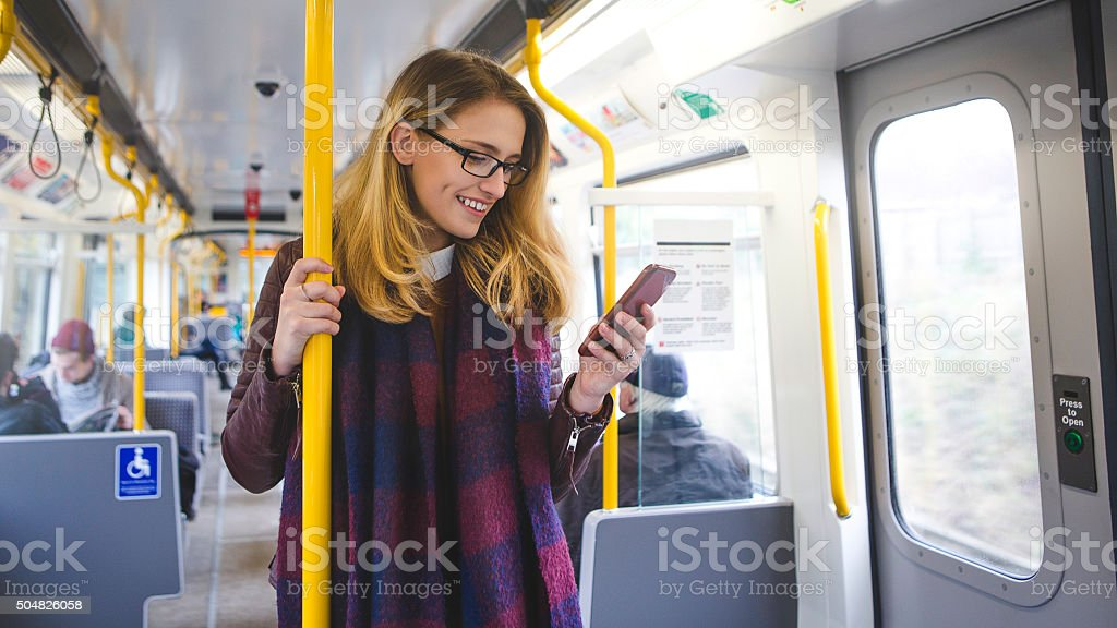 Young hipster styled woman standing on a train using a smartphone....