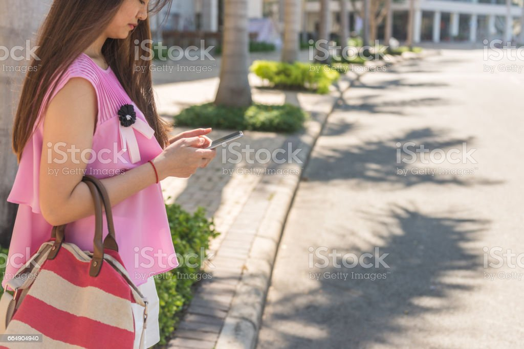 Using smartphone on the sidewalk while waiting for taxi stock photo